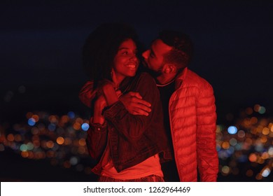 real millennial couple smiling happy in love, cute intimate moment with city lights in background