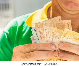 Real, Money from Brazil. Dinheiro, Brasil, Reais, Currency. Man holding in hand a group of Real banknotes.