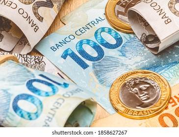 Real, money from Brazil. Dinheiro, Reais, Brasil, Real Brasileiro. A group of brazilian banknotes and coins on a desk.