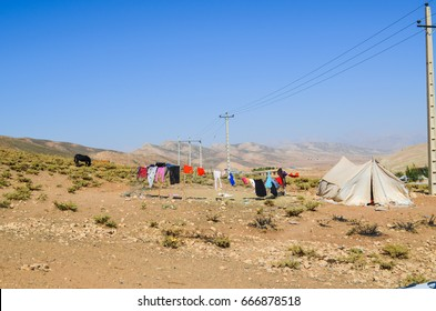 Real nomads camp stand with a black horse, a nomadic tent and clothing air drying, Iran