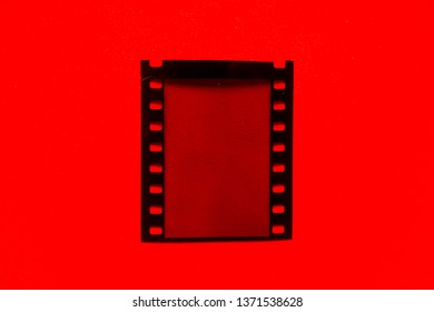 Real and original 35mm movie or film strip on red background, detail shot of old blank and empty film material, just blend in your work