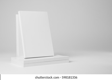 Real paperback white book over a stack of books on a gray background