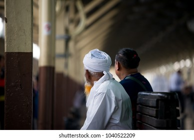 A real people, candid of a long yellow white mustache with white Muslim outfit in train station looking for train coming