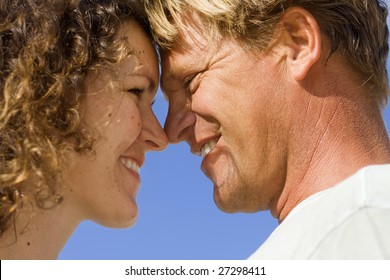 Real people. Real love. Romantic couple on the blue Caribbean sky background.