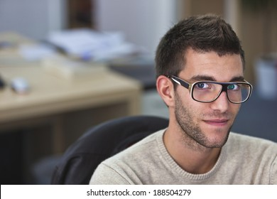 Real People - Portrait of a smart an handsome young man in office with available light