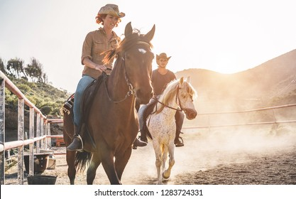 Real people riding horses inside corral - Wild couple having fun in equestrian ranch  - Training, culture, passion, excursion, healthy lifestyle, sport concept - Focus on man face