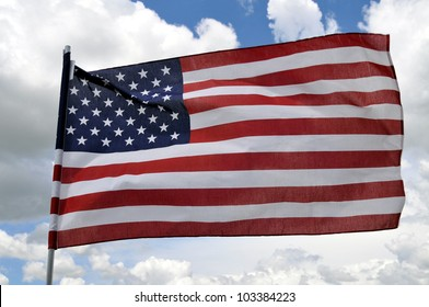 A real photo of the American flag in a very strong wind against a cloudy sky
