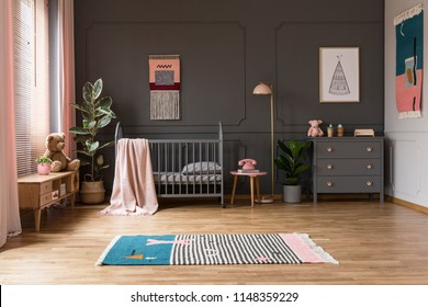 Real photo of a baby crib in a grey child's room interior, next to a cupboards, lamp and plants
