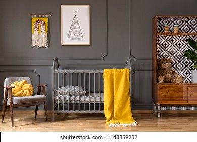 Real photo of a baby room with yellow cot standing between an armchair and a cupboard with teddy bear and a plant in child's interior
