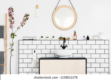 Real photo of a bathroom interior with a round mirror, sink with black faucet and pink flower