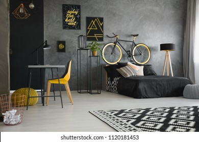 Real photo of a black bed standing against raw, gray wall in modern teenager's bedroom interior with a bike on the bedhead, yellow chair, desk and wooden lamp