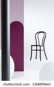 Real photo of a black chair standing against white wall in a bright studio interior with a purple pillar