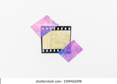 real photo of blank or empty 35mm film frame with shiny holo stickers on border edges on white background, cool poster idea