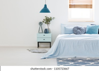 Real photo of a blue and white bedroom interior with wooden nightstand between a light blue bed and an empty wall. Paste your armchair here