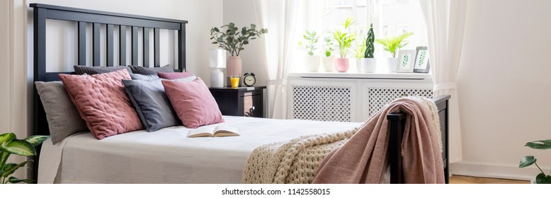 Real photo of bright bedroom interior with plants on windowsill, open book on king-size bed with pastel cushions and black bedhead and window with curtains