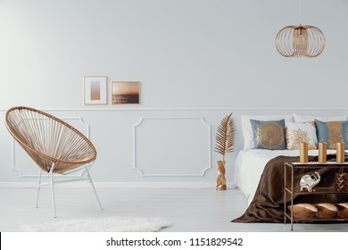 Real photo of bright bedroom interior with gold decor, framed photos hanging on wall with molding, double bed and chair