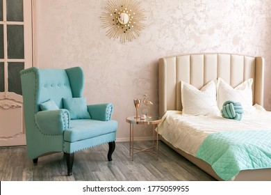 Real photo of a bright bedroom bedroom in pink, blue and gold colors, with a large window, vintage doors, a beige bed, a blue comfy armchair, a gold mirrored coffee table