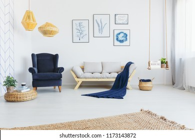 Real photo of a bright living room interior with a comfy armchair, sofa, wicker lamps and botanical graphics on the wall