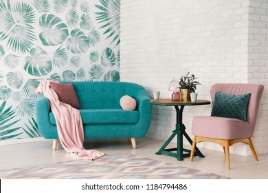 Real photo of bright sitting room interior with wooden end table with fresh plant and two mugs standing between dirty pink armchair and turquoise lounge with pillows and blanket