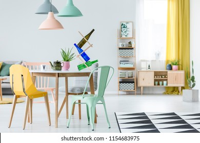 Real photo of a colorful dining room interior with a dining table, chairs, bottle holder, lamps and wooden cupboards in the blurred background