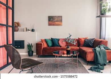 Real photo of a comfy living room interior with a round table on gray rug, wicker armchair and red corner sofa