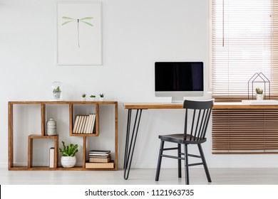 Real photo of a computer with empty screen standing on a wooden desk in bright freelancer's office interior with black chair and bookcase