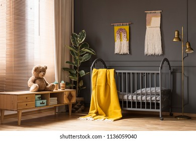 Real photo of a cot with a yellow blanket standing between a low cupboard with a teddy bear and a lamp in baby room interior