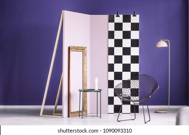 Real photo of a creative arrangement of furniture in purple interior with gold frame, metal table, black chair and lamp