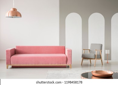 Real photo of a creative living room interior decorated with arches, pink sofa and retro armchair