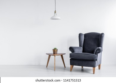 Real photo of dark grey armchair standing next to wooden end table with cactus in bright room interior with empty space for your cupboard