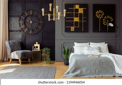 Real photo of dark grey bedroom interior with molding and paintings on walls, double bed with pillows, gold lamp and floral armchair