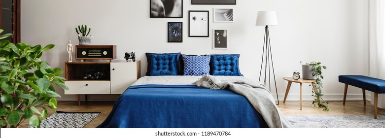 Real photo of an eclectic bedroom interior with graphics on a wall, blue pillows and radio on a cupboard