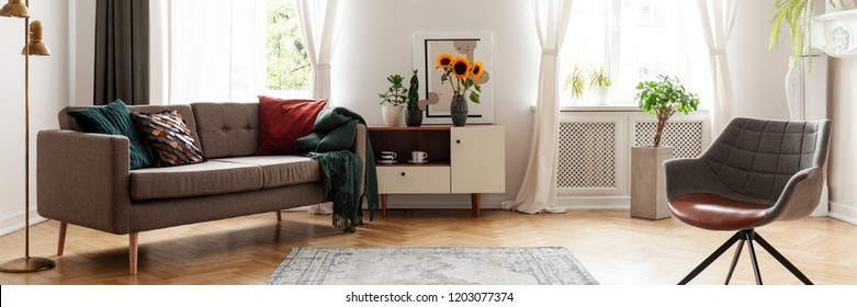 Real photo of an eclectic living room interior with a sofa, armchair and sunflowers in a vase