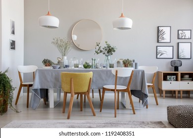 Real photo of an elegant dining room interior with a laid table, chairs, mirror on a wall and lamps