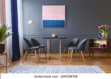 Real photo of four chairs standing around a table in a spacious dining room interior next to a patterned rug, shelf, lamp and grey wall with a painting
