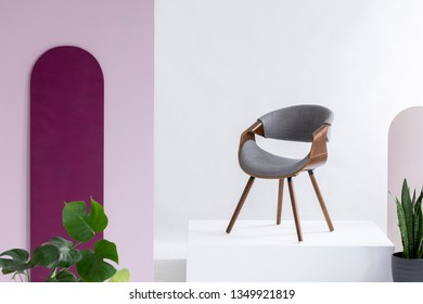 Real photo of a gray, fleece and leather chair standing on a podium in a living room interior with plants