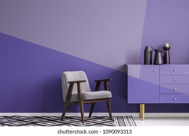 Real photo of a gray, wooden armchair on patterned, black and white rug in creative living room interior with geometric, violet wall and cupboard