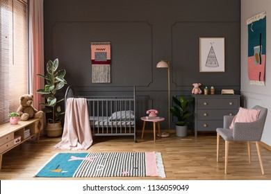 Real photo of a grey crib standing next to a pink stool, a lamp and cupboard in grey baby room interior also with armchair, rug and poster