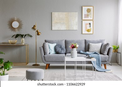 Real photo of a grey sofa with cushions and blanket standing in elegant living room interior behind a white table and next to a gold lamp and grey wall with posters