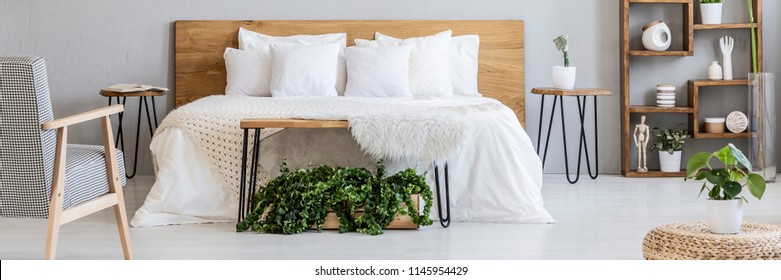 Real photo of king-size bed with white sheets and many pillows standing in grey bedroom interior with hairpin bedside tables