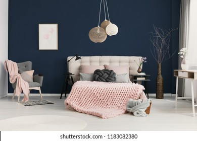 Real photo of knot cushion and pastel pink coverlet placed on double bed in elegant hotel room interior with simple poster on dark blue wall, armchair in the corner and twigs in tall vase