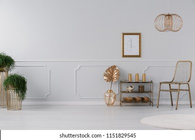 Real photo of living room interior with fresh plants, poster on wall, gold chair and small rack with decor and candles