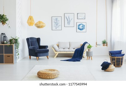 Real photo of a living room interior with blue accents, wicker pouf on the floor and poster collection
