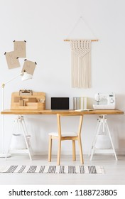 Real photo of a modern home offfice interior with a desk, laptop, sewing machine, chair and macrame on a wall. Empty screen, place your logo