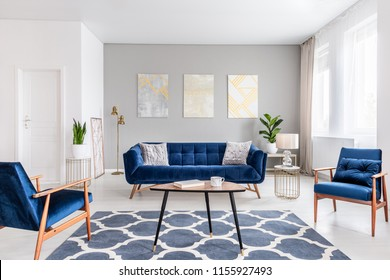 Real photo of a modern living room interior with a sofa, armchairs, table, paintings and patterned carpet
