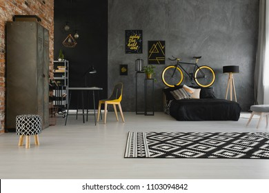 Real photo of a modern, open space apartment interior with a bicycle on the bedhead of a black bed and yellow chair at a desk