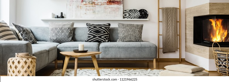 Real photo of modern painting placed on the shelf above grey sofa with patterned pillows standing in bright sitting room interior with blanket on wooden ladder and fireplace