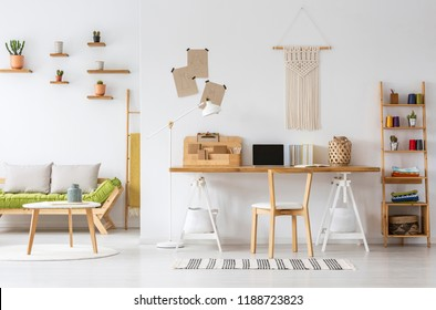 Real photo of a natural home office interior desk organizer, macrame on a wall, shelves and couch