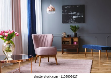 Real photo of a pink armchair standing on a rug and under a lamp in spacious living room interior, next to a table with flowers and in front of a shelf next to a grey wall with dark painting - Shutterstock ID 1105805627