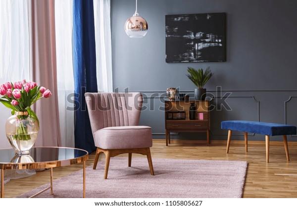 Echte foto van een roze fauteuil staande op een tapijt en onder een lamp in ruim woonkamerinterieur, naast een tafel met bloemen en voor een plank naast een grijze muur met donker schilderij